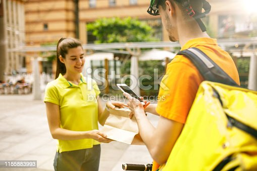 istock Young man as a courier delivering package using gadgets 1155883993
