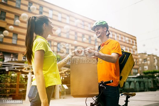 istock Young man as a courier delivering package using gadgets 1155883994