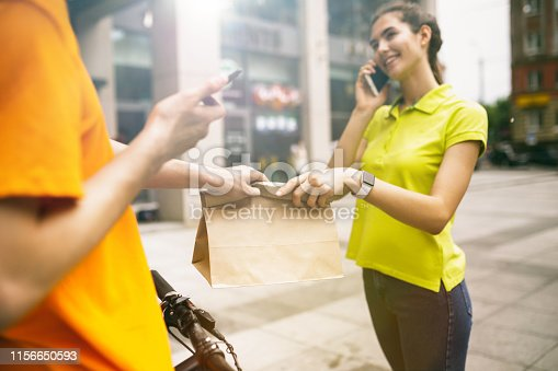 istock Young man as a courier delivering package using gadgets 1156650593