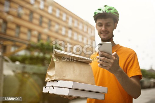 istock Young man as a courier delivering pizza using gadgets 1155884012