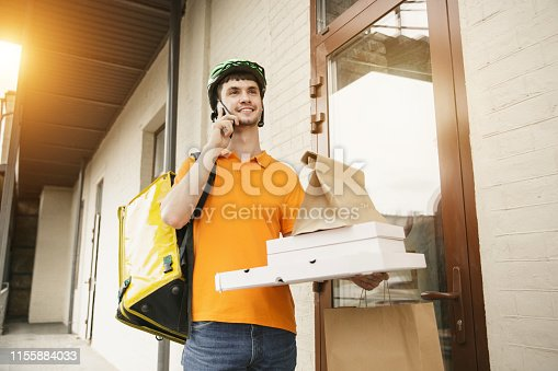 istock Young man as a courier delivering pizza using gadgets 1155884033