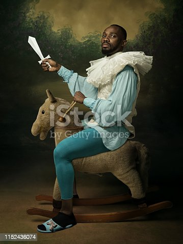 Young man as a medieval knight on dark background. Portrait of male model in retro costume. Goes on a war with his best friend. Human emotions, comparison of eras, facial expressions concept.