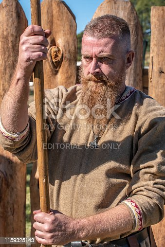 Lismore,NSW,Australia:June 22,2019. Young man as a Viking, guards the entrance at the Viking Festival. Every year, on the Winter solstice, a group of Viking followers build a Viking village in the NSW town of Lismore. For two days they live as Vikings, dressing ,playing ,eating, speaking, fighting as the ancient Vikings did. This event is free and open to the public. It is held on a recreation ground in the town.