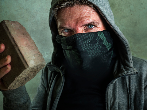 young man as fanatic and aggressive anarchist rioter . furious and scary violent anti-system protester in face mask throwing brick looking hostile at fighting riot in radical demonstration