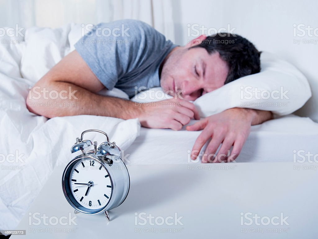 Joven atractivo hombre durmiendo en la cama - Foto de stock de Acogedor libre de derechos