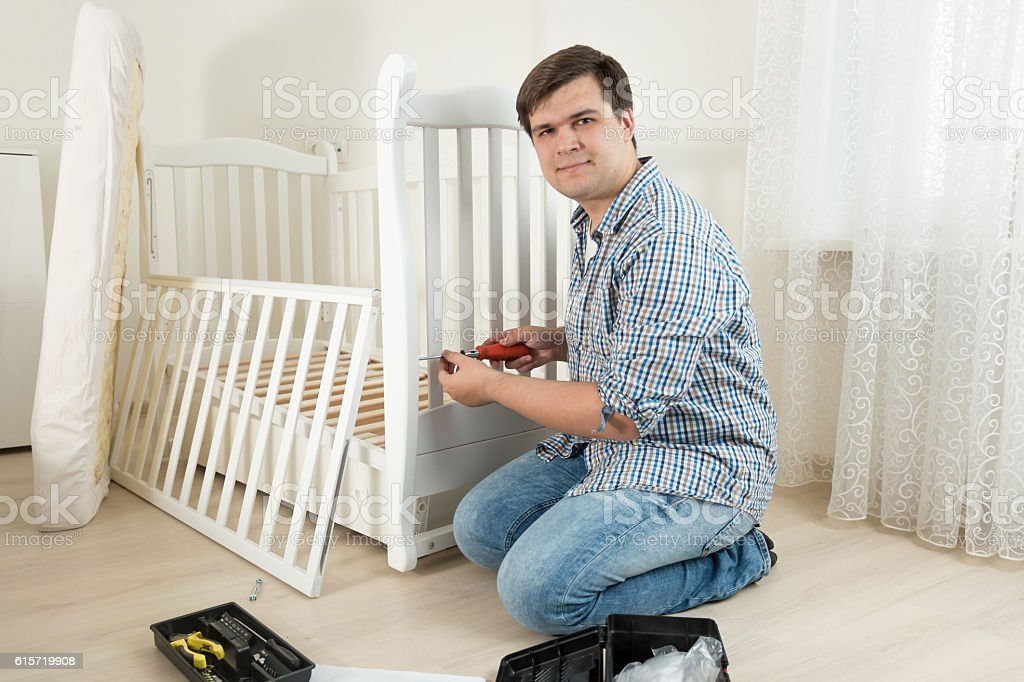 Young man assembling wooden cot in nursery for expectant baby stock photo