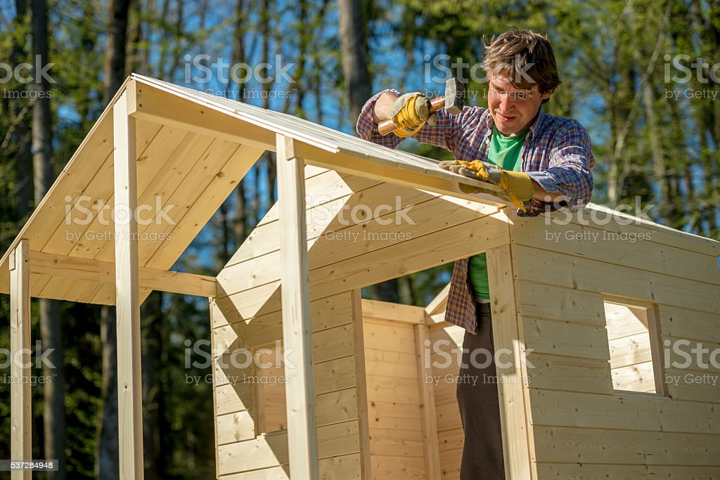 Young man assembling wooden play house stock photo
