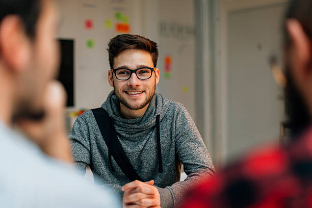 Young man at a job interview. Young man at a job interview talking with two developers. They are running startup developer company from their home. Selective focus to young candidate over their shoulders. eastern europe stock pictures, royalty-free photos & images