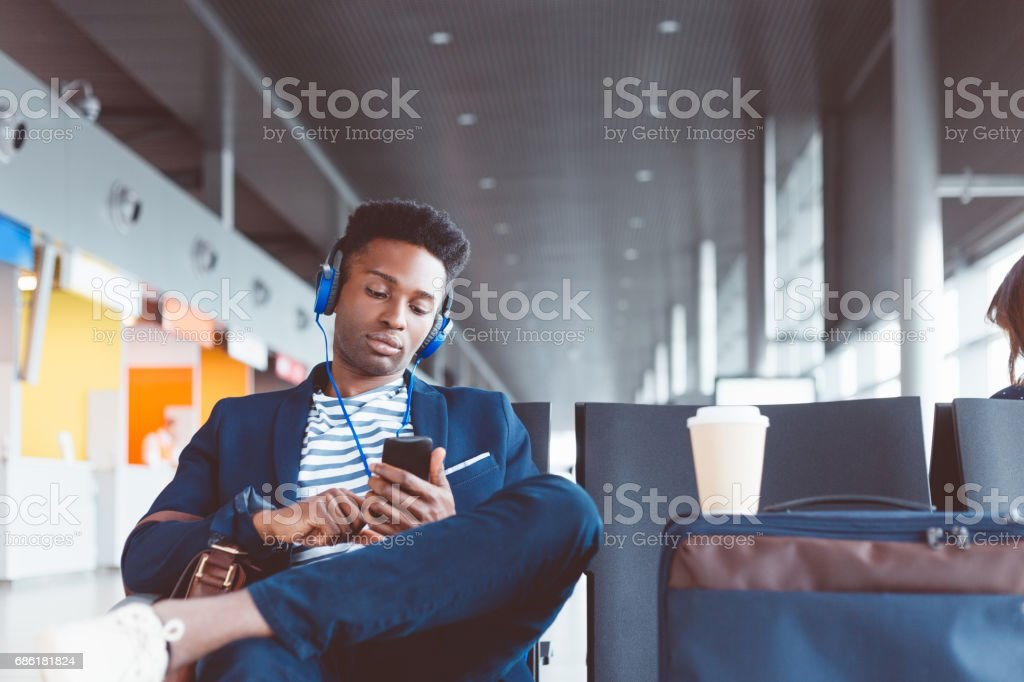 Young man at airport lounge listening music stock photo