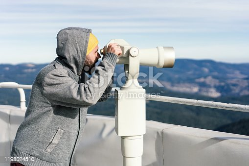 Side-view image of young male hiker looking through tourist binoculars