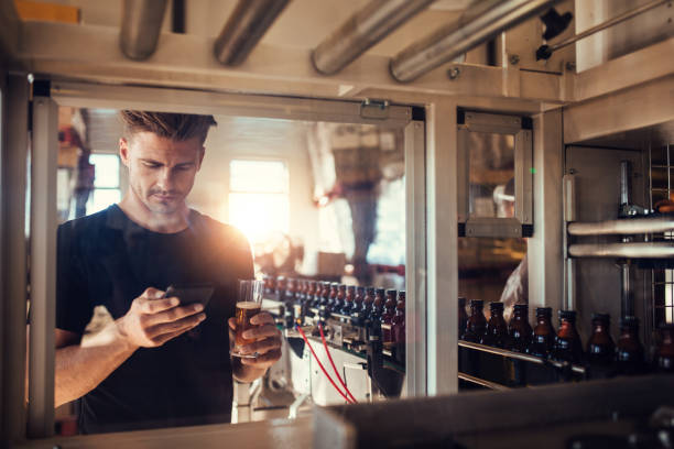 Young man at brewery plant using mobile phone stock photo