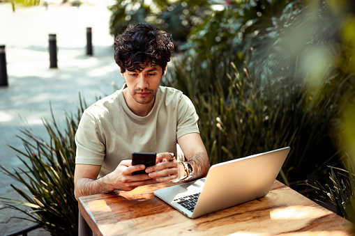 Young man working from coffee shop. He is using mobile phone and laptop
