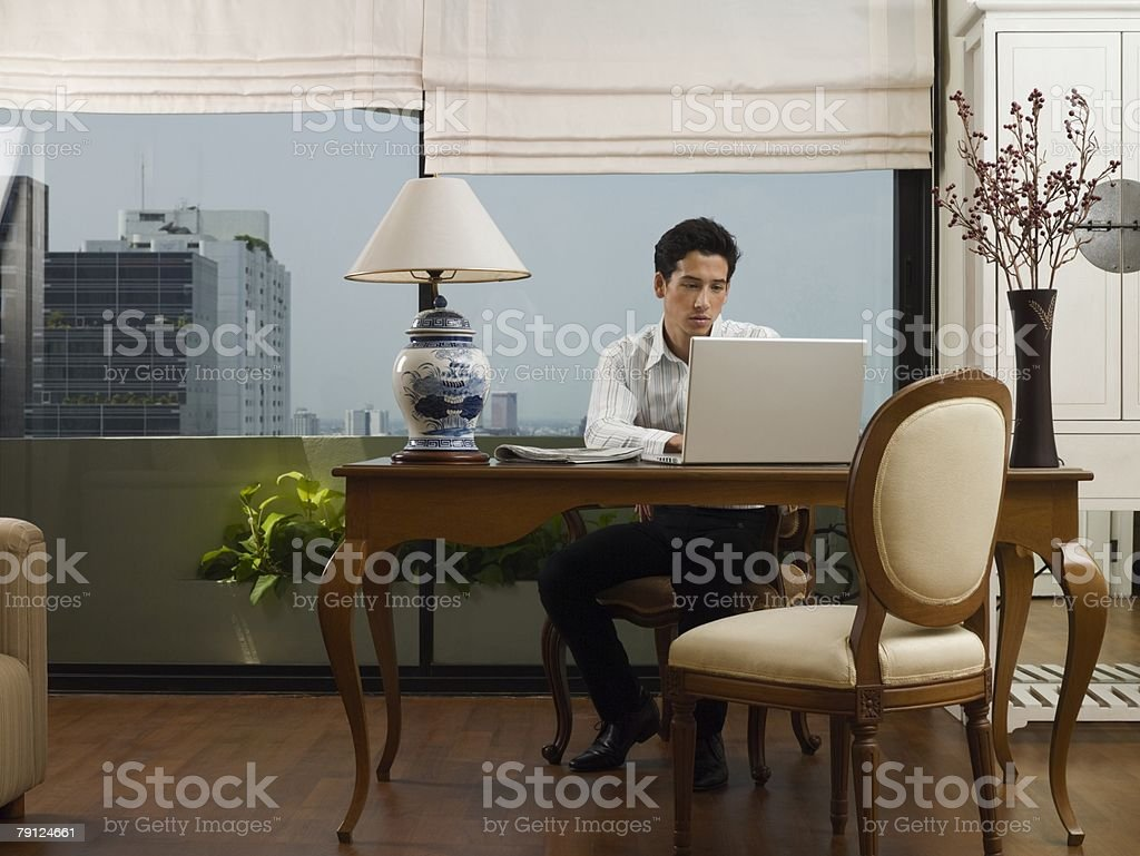 Young man at desk using laptop royalty-free stock photo