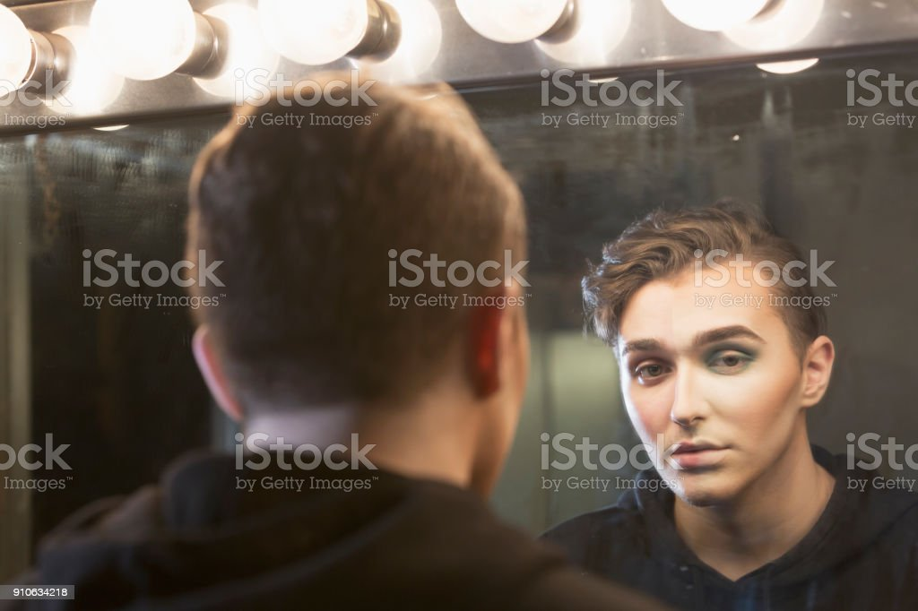 Young man at dressing room mirror, with make-up stock photo