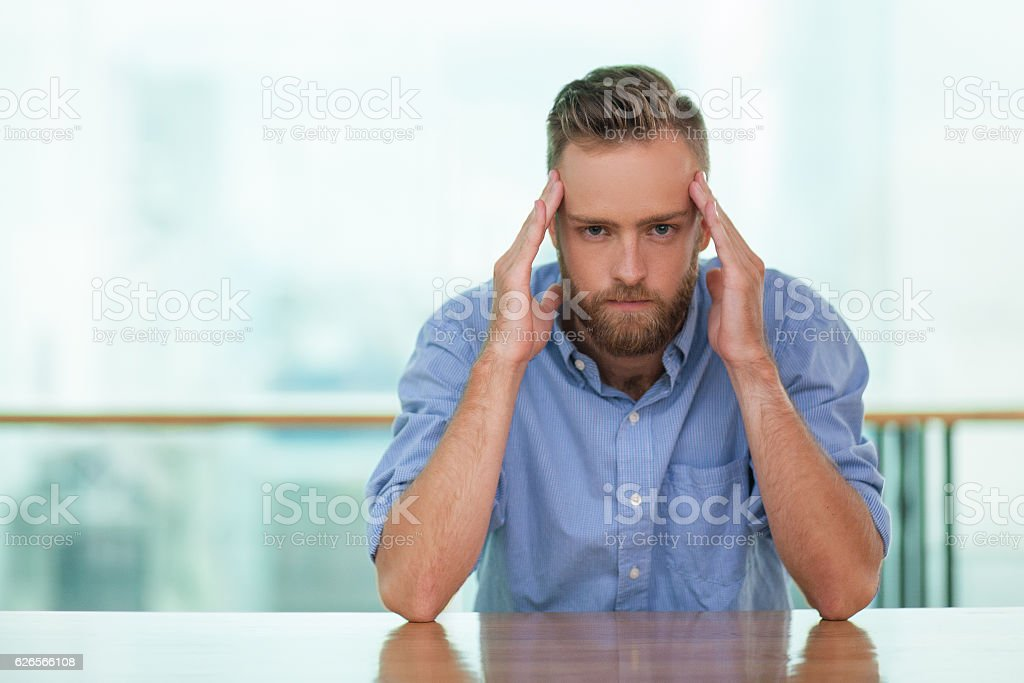 Young Man at Empty Cafe Table with Intense Look stock photo