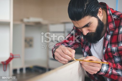 452592895 istock photo Young man at his apartment making furniture 934707122