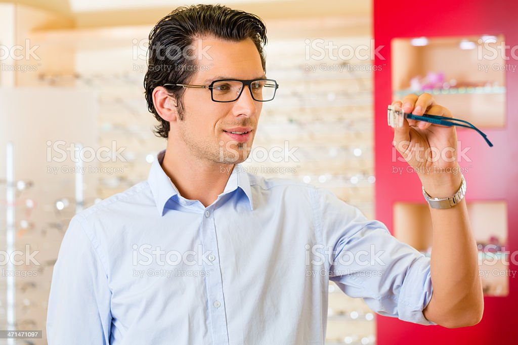Young man at optician with glasses royalty-free stock photo