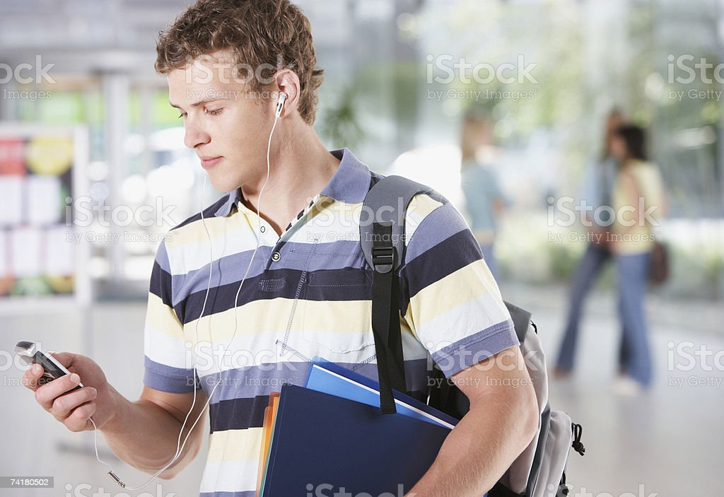 Young man at  school with mp3 player and earbuds royalty-free stock photo