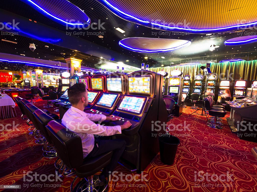 Young man at Slot machine in Casino stock photo