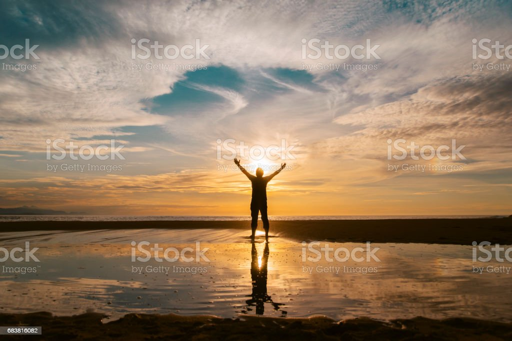 Young man at sunset and reflection stock photo