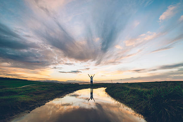 Young man at sunset A young man reflected on a puddle at sunset religion stock pictures, royalty-free photos & images