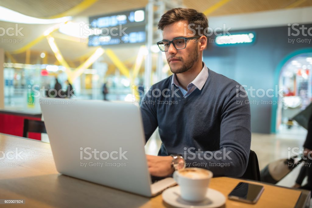 young man at the airport working with laptop using his mobile phone and drinking coffee waiting for his flight stock photo