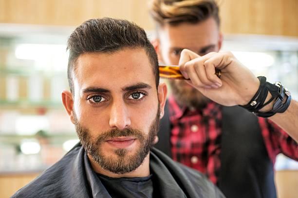 jeune homme dans le salon de coiffure - barbier coiffeur photos et images de collection