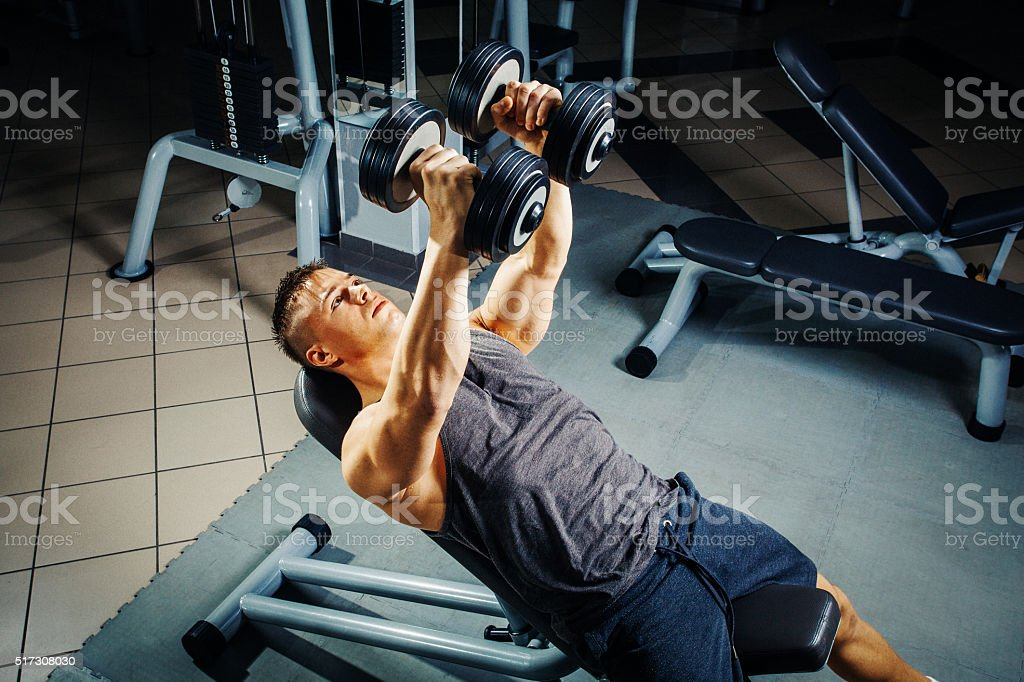 Young man at the gym chest workout with dumbbells stock photo