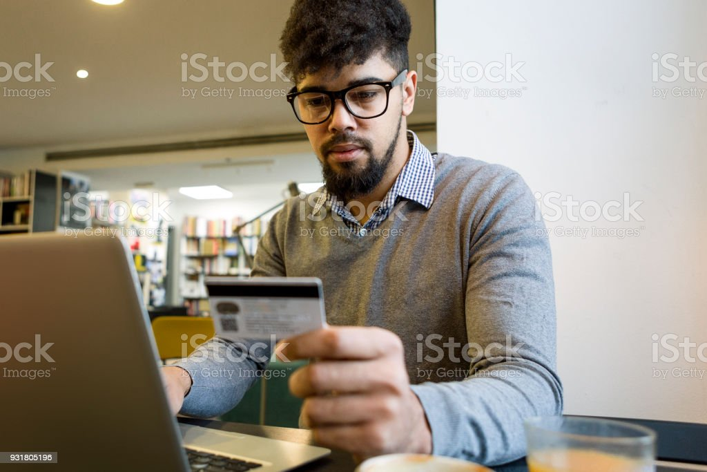 Young man at the library making credit card purchase online using laptop stock photo