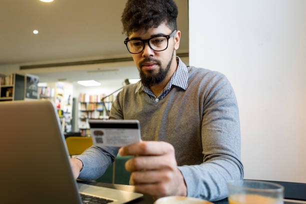 young man at the library making credit card purchase online using laptop - spending money stock photos and pictures