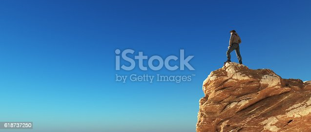 istock Young man at the top of the mountain 618737250