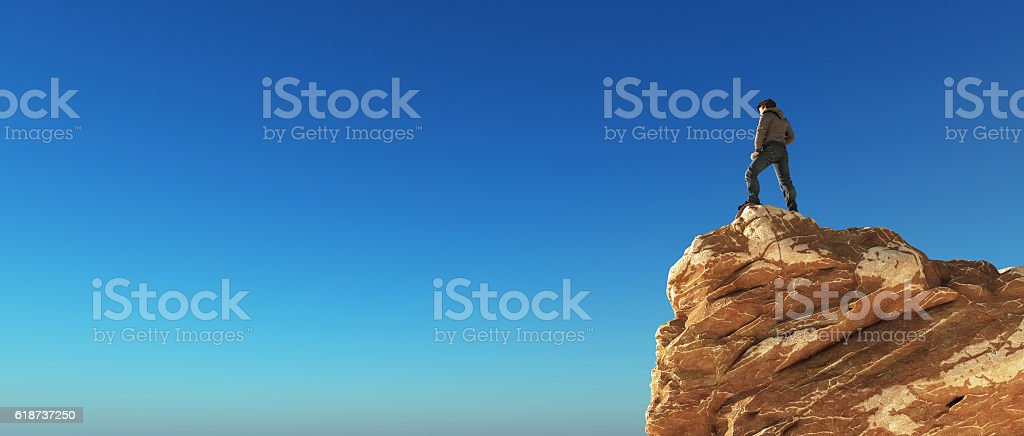 Young man at the top of the mountain stock photo