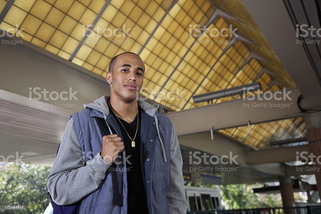 Young man at train station royalty-free stock photo