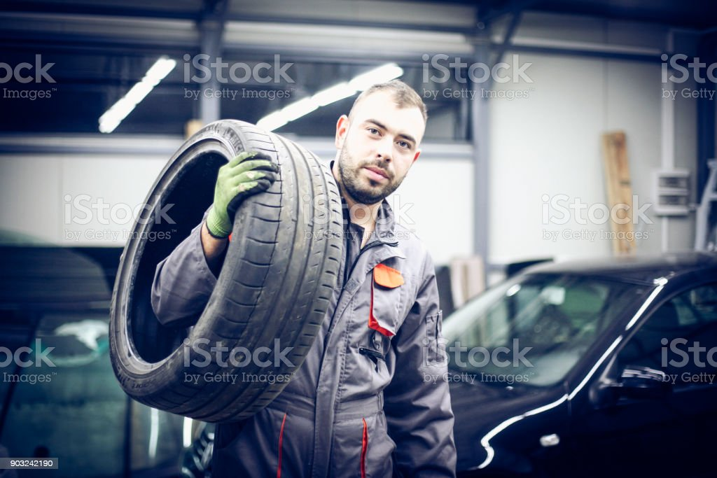 Young man at workshop carrying tires. Portrait. stock photo