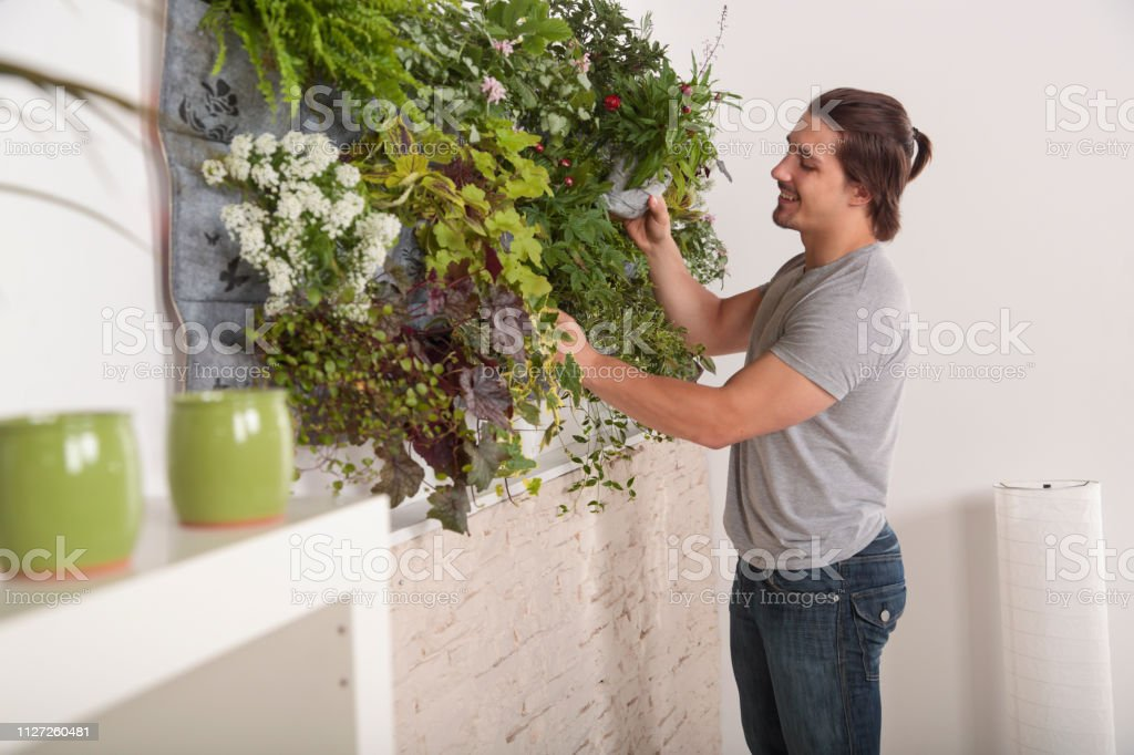 Man holding gardening equipment for attending flowers in his vertical...