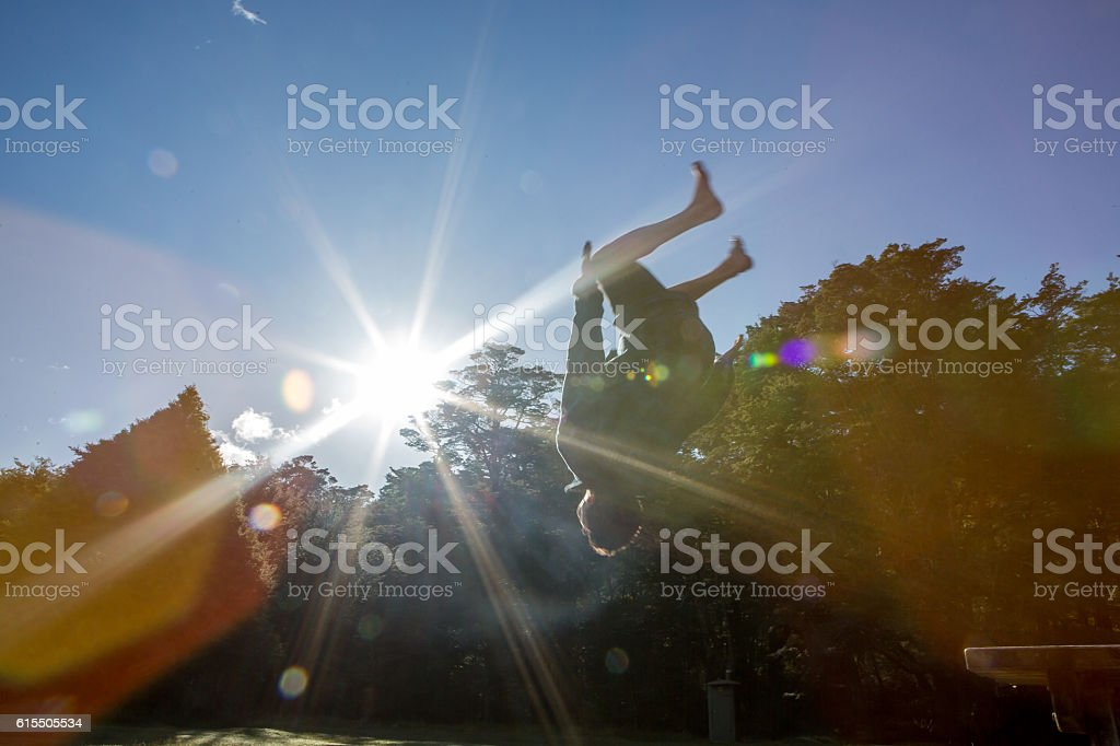 Young man backflipping mid-air against blue sky stock photo