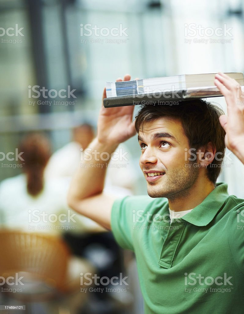 Young man balancing books on his head and smiling royalty-free stock photo