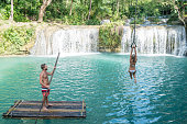 Young couple having fun at a beautiful waterfall on Siquijor Island in the Philippines. People travel nature adventure concept. Two people romance love sharing enjoying outdoors and tranquillity in a peaceful environment, traveler concept