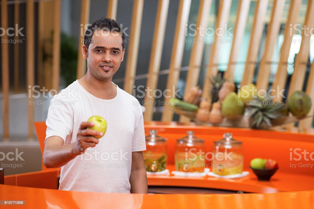 Young Man behind Sport Bar Counter Offering Apple stock photo