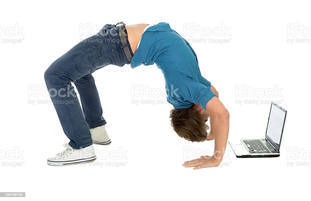 Young man bending over backwards while using laptop stock photo