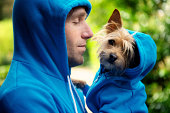 Young man holding his best friend dog in matching blue hoodies in bright green park background outdoors