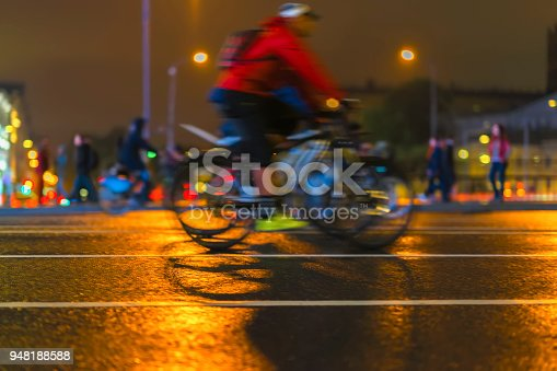 929609038istockphoto Young man biker riding bicycle during at night on a city street. Abstract blurred sport background 948188588