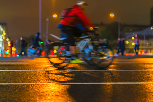 929609038 istock photo Young man biker riding bicycle during at night on a city street. Abstract blurred sport background 948188588