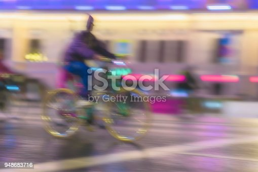 929609038istockphoto Young man biker riding bicycle during at night on city street, urban scene. Abstract blurred modern background 948683716