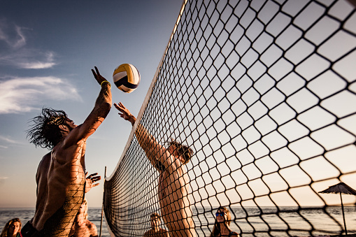 Group of friends having fun while playing volleyball on the beach. One man is trying to block his friend.