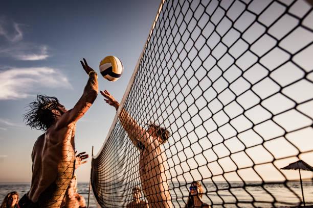 joven bloqueando a su amigo mientras jugaba al voleibol de playa en el día de verano. - juego de vóleibol fotografías e imágenes de stock