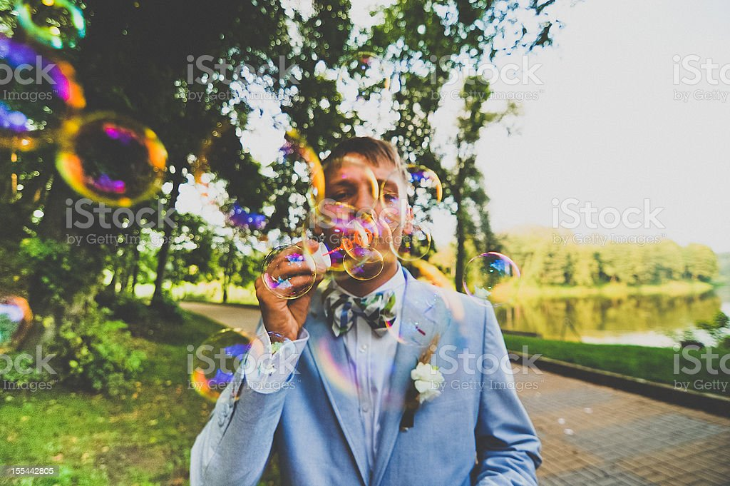 Young man blowing bubbles stock photo