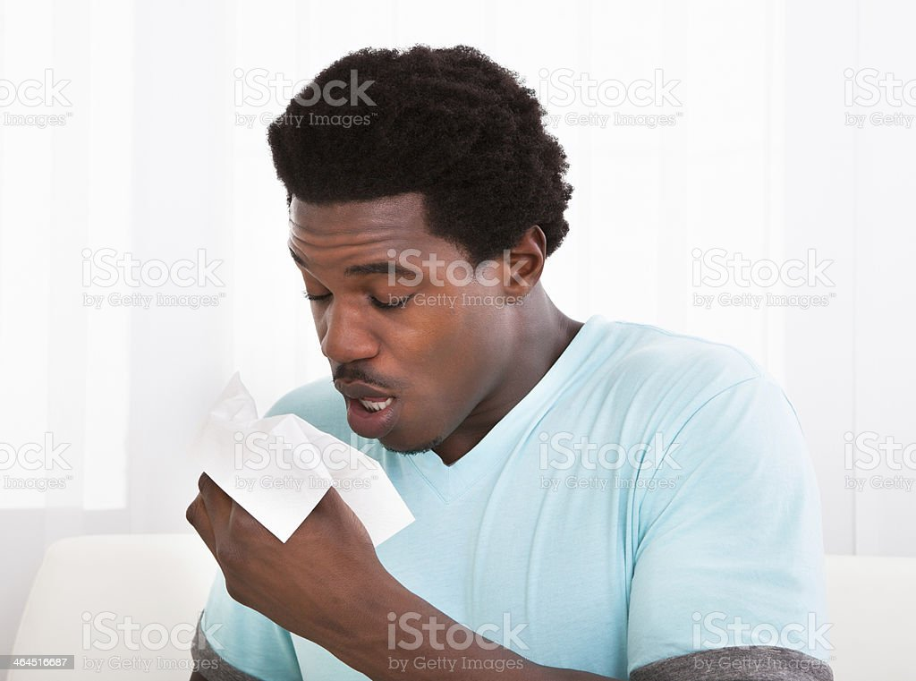 Young Man Blowing His Nose In A Tissue stock photo