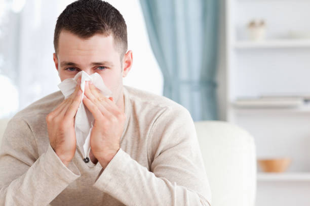Young man blowing his nose Young man blowing his nose in his living room human parainfluenza virus stock pictures, royalty-free photos & images