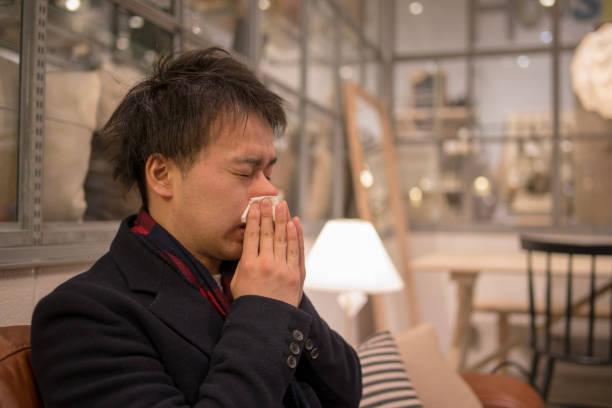 若い男のリビング ルームで鼻をかむ - くしゃみ 日本人 ストックフォトと画像